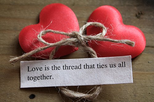 two silky love hearts next to a loving quote and a tied knot on a wooden surface