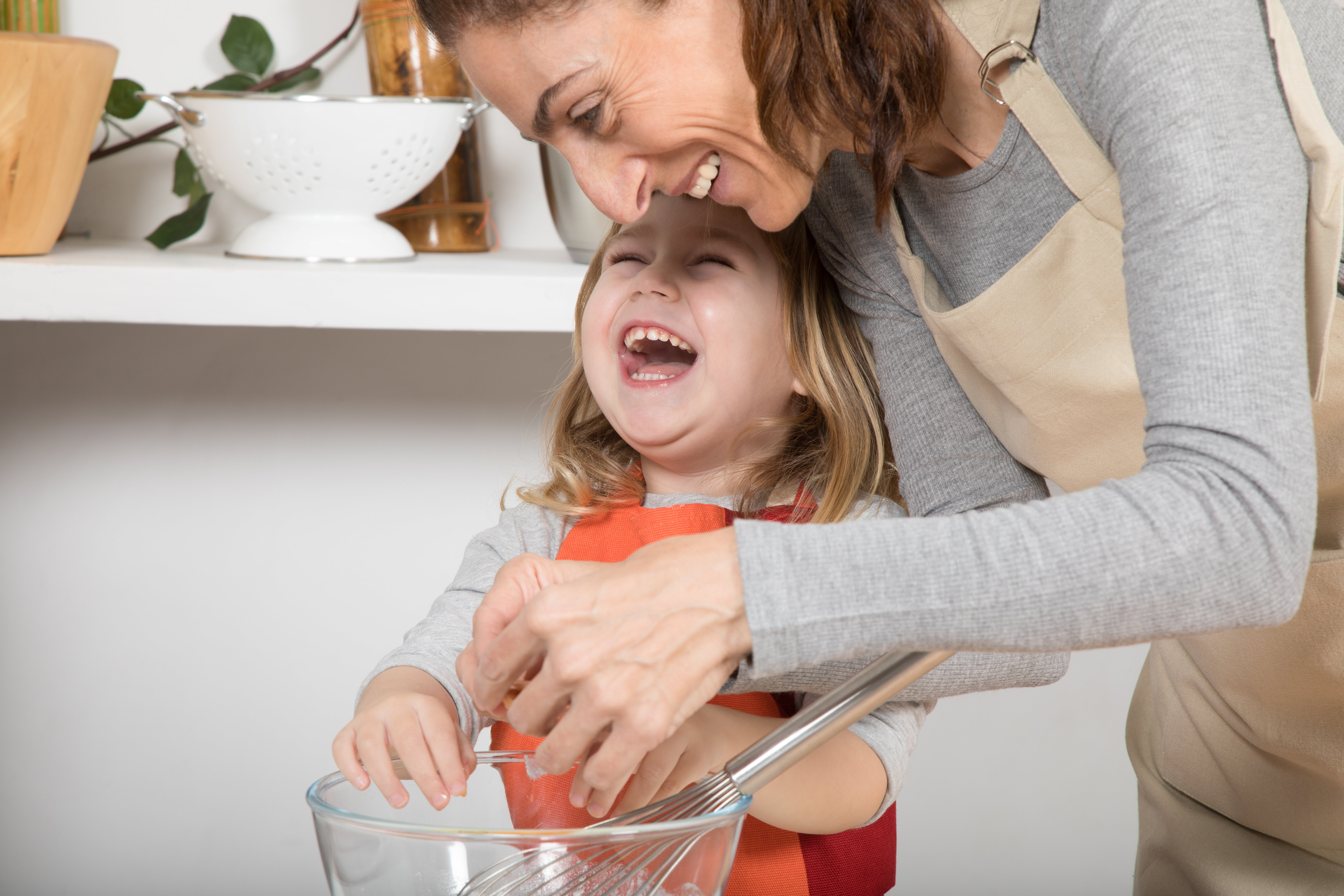 funny three years old child and woman mother with beige apron in teamwork cooking a sponge cake at kitchen home laughing happy together